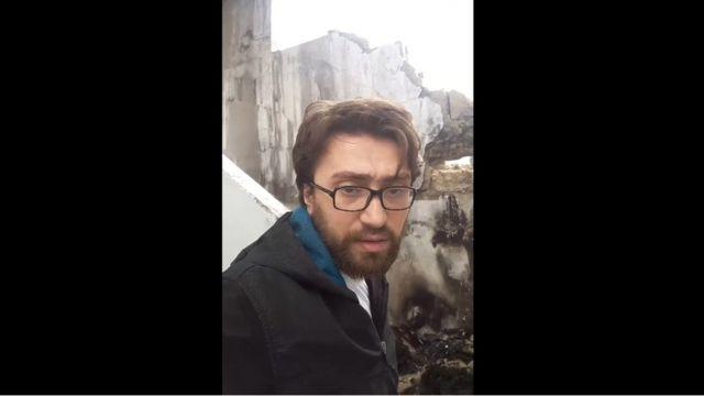 Yerli fəal və jurnalist Salah Ashkar şərqi Hələbdə qaldığı binaya dəyən zərbənin yerini göstərir.
