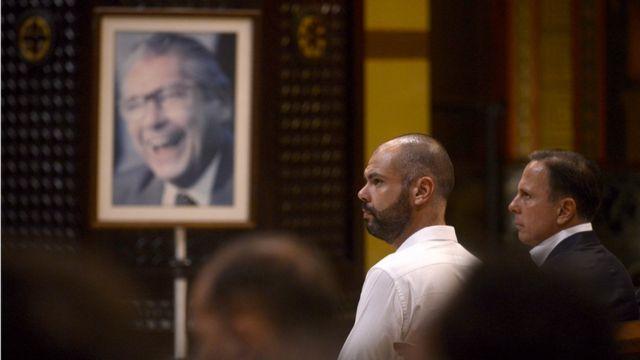 Bruno Covas ao lado de João Doria e foto de Mário Covas ao fundo;