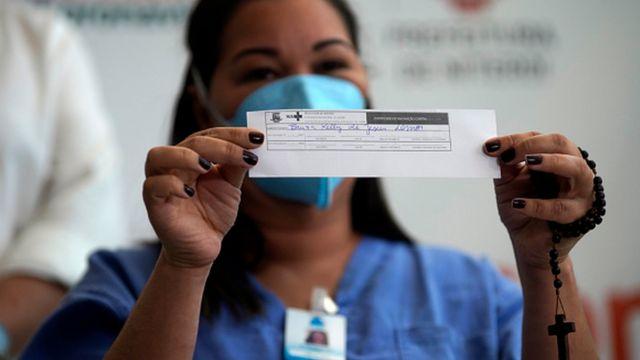 Mulher segura comprovante de vacinação
