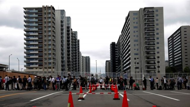 Fences and queue of people outside the Olympic Village