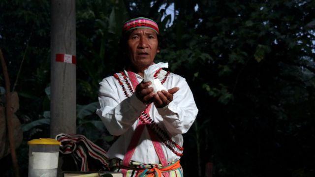 Shainkiam Yampik Wananch, diácono ordenado por la Iglesia Católica, sostiene hostias durante una liturgia con indígenas Achuar en una capilla en Wijint, una aldea en la Amazonía peruana, en Perú, el 20 de agosto de 2019.
