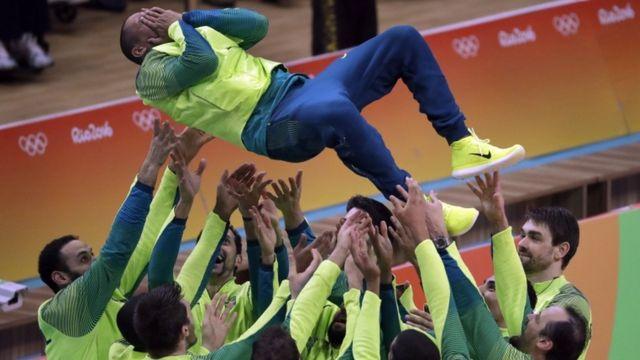 Jogadores do vôlei celebram a vitória, jogando o líbero Serginho para o alto
