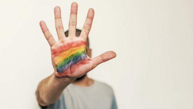 Pessoa com arco-íris na mão