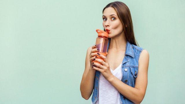 Mujer bebiendo agua.