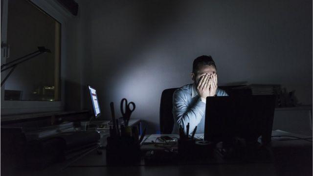 Un hombre se tapa la cara con las manos en en una oficina oscura.