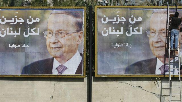 رجل يقوم بوضع ملصق إعلاني لميشال عون الذي اختير رئيسا للبنان