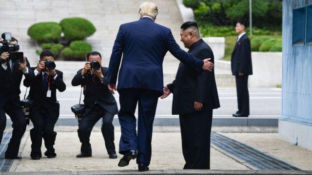 Г-н Трамп ступает на северную сторону военной демаркационной линии, разделяющей две Кореи.