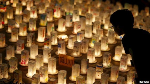 """A boy looks at candles during a candlelit memorial event to mourn the victims of the 1945 atomic bombing at Nagasaki""""s Peace Park in western Japan"""