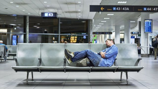 Un hombre dormido en un aeropuerto