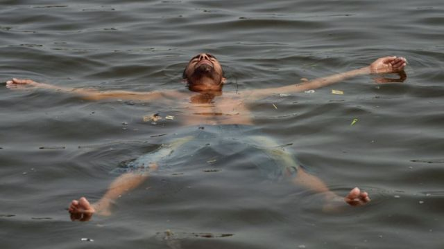 A Pakistani youth cools off in the sea during a heatwave in Karachi
