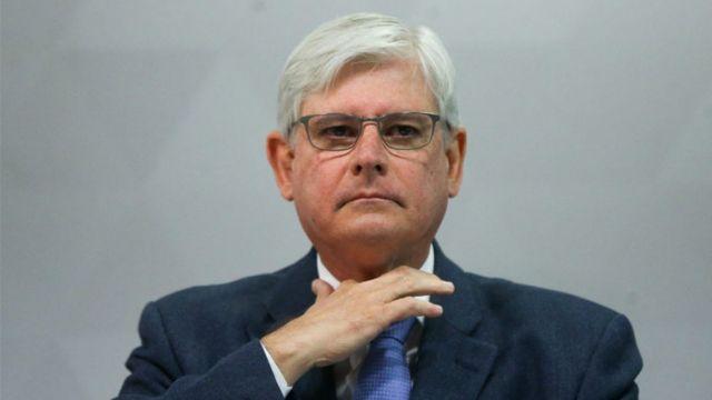 O procurador-geral Rodrigo Janot com a mão direita no pescoço