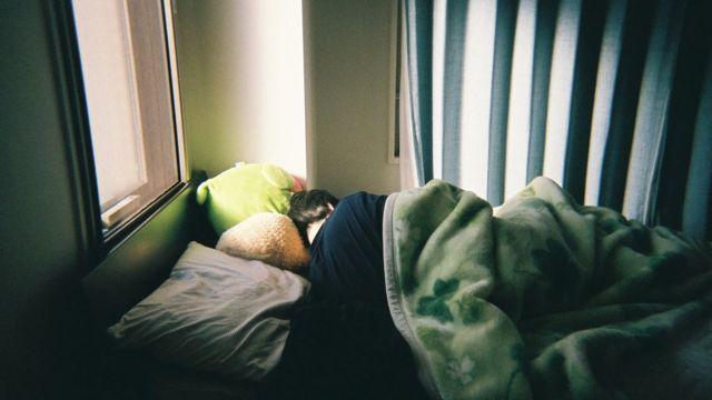 Pessoa de cabelo preto e curto, sem rosto aparecendo, deitada em cama