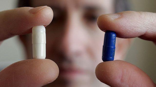 Un hombre con dos píldoras en las manos