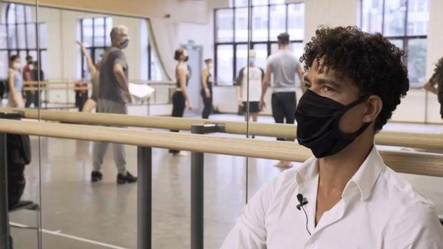 Carlos Acosta, usando máscara, em uma sala de dança