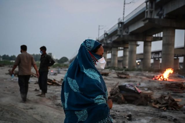 Parentes de vítima da covid-19 em cerimônia fúnebre de cremação às margens do Ganges, em 16 de maio