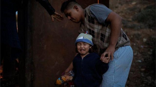 Una niña se dispone a saltar la vaya ayudada por sus familiares