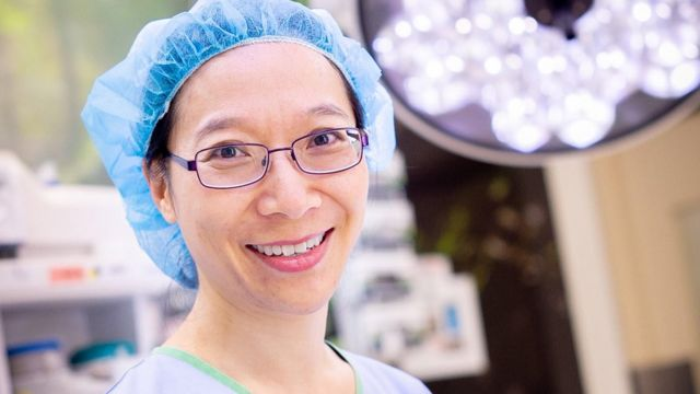 Dr Rhea Liang smiling in an operating theatre