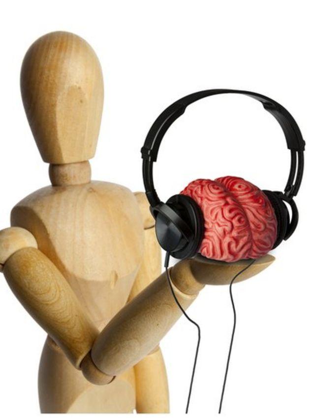 Muñeco de madera sosteniendo en una mano un cerebro con audífonos.