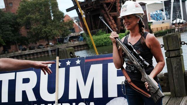 Una mujer que apoya a Trump sostiene un arma larga.