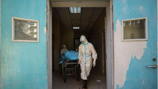 Médicos carregam paciente morto pelo coronavírus na China
