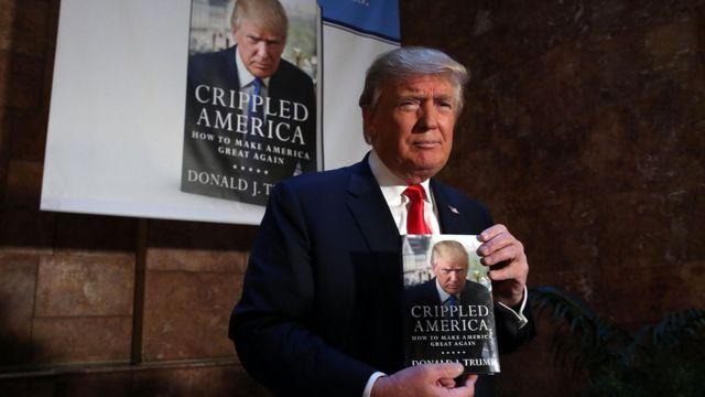 """Дональд Трамп со своей новой книгой """"Изувеченная Америка: как сделать Америку снова великой"""", 3 ноября 2015 года в Нью-Йорке"""