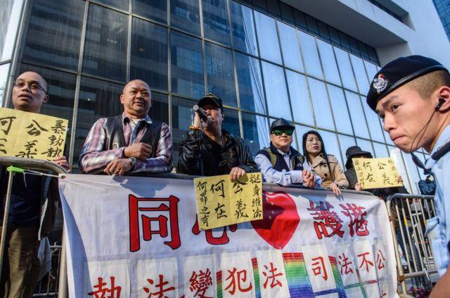 """在庭外支持警方执法的团体手持""""公义何在?""""的标语牌示威。"""