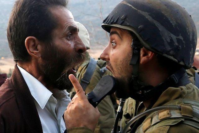 一名巴勒斯坦男子與一名以色列士兵在爭吵。