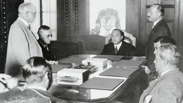 Genaro Estrada, sentado a la cabeza de la mesa