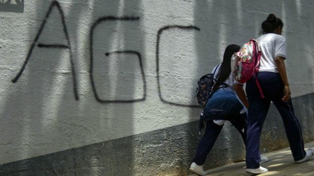 """Dos adolescentes caminan frente a un mural con la sigla """"AGC"""" que significa Autodefensas Gaitanistas de Colombia."""