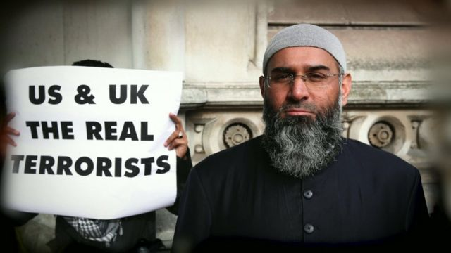 Anjem Choudary with a protestor holding banner stating 'US & UK The Real Terrorists'.