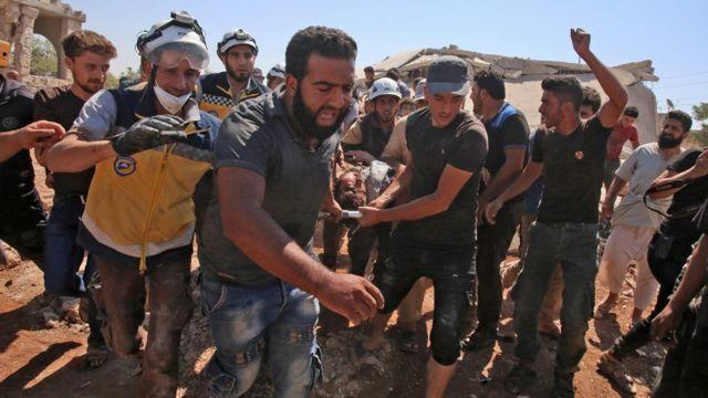 Membros da defesa síria, conhecidos como capacetes brancos, retiram feridos de escombros depois de um ataque russo na província de Idlib em julho de 2019