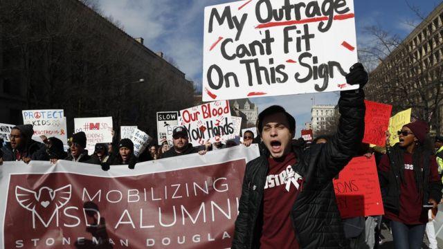 """Мајкл Вајсман, 18, ђак средње школе Марџори Стоунмен Даглас, у којој је погинуло 17 ученика у фебруару, носи паролу са натписом """"Мој бес не може да стане на овај знак"""""""