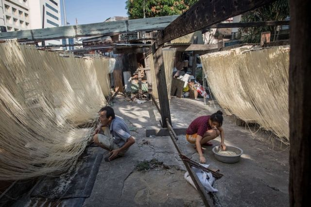 Two Thai men making traditional Chinese style noodles in a Bangkok market