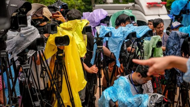 Dozens of media cameras are pictured, covered with makeshift waterproof protection