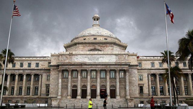 Capitolio de Puerto Rico con las banderas de Estados Unidos y Puerto Rico.