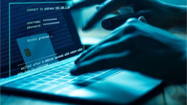 Mãos digitando em um laptop invadindo uma conta pela internet