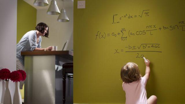 Imagem mostra criança escrevendo fórmulas matemáticas na parede de casa