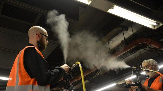Участники эксперимента распыляют частицы на платформе линии 4/5/6 на одной из нью-йоркских станций
