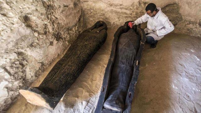 Археолог осматривает мумии в некрополе Эль-Ассасиф в Египте