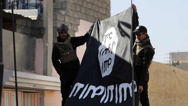 Soldiers from the Iraqi army hold an IS flag upside down in a north-east district of Mosul