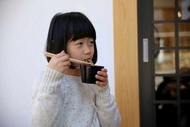 Cute Japanese girl, slurping noodles from a black bowl