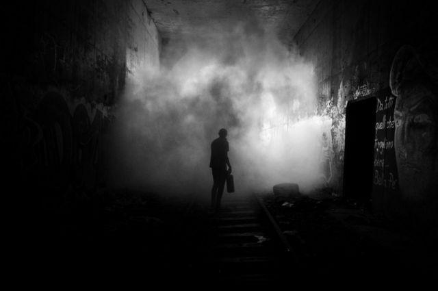 Уличный художник идет по шпалам в темноте