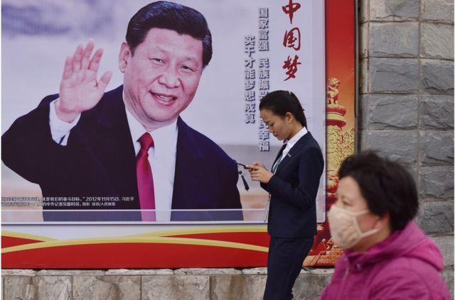 """人们走过北京一条道路旁的""""中国梦,人民的梦""""海报,上面有中国国家主席习近平挥手的照片。"""