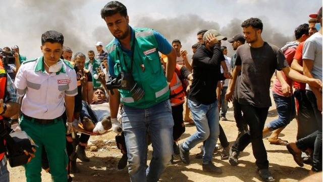 Emergency services and Palestinians carry a wounded protestor during clashes with Israeli security forces near the border between Israel and the Gaza Strip, east of Jabalia on May 14, 2018