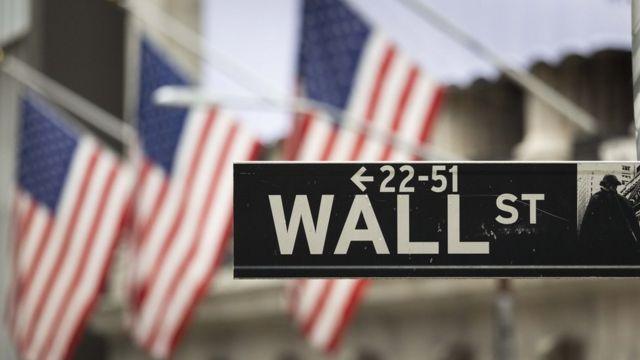 Placa de Wall Street em Nova York com um fundo de bandeiras dos Estados Unidos
