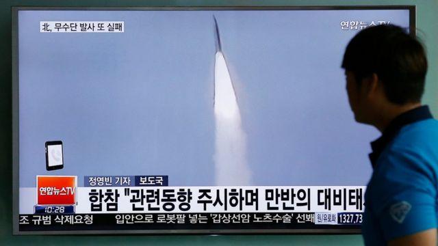 北朝鮮によるミサイル発射実験を伝えるテレビニュースを見る男性