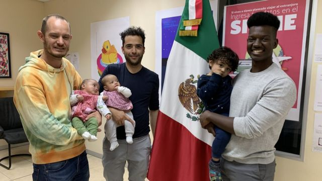 Phillip Lühl, Guillermo Delgado y un amigo de la pareja cargando a las gemelas, Paula and Maya, y a Yona.
