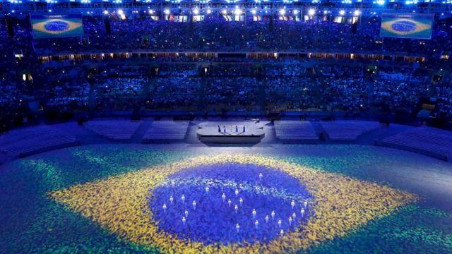 luzes que traziam nas roupas depois formaram as estrelas da bandeira brasileira projetada no estádio.