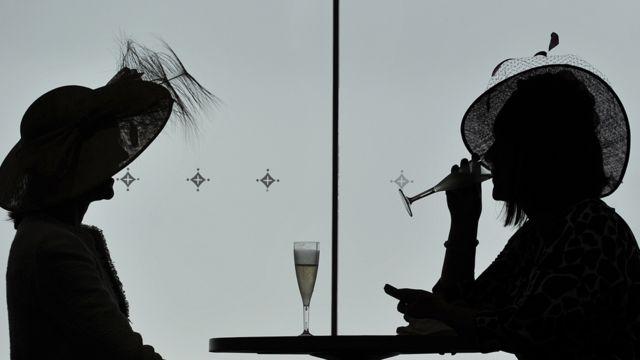 Silhueta de duas mulheres bebendo champagne