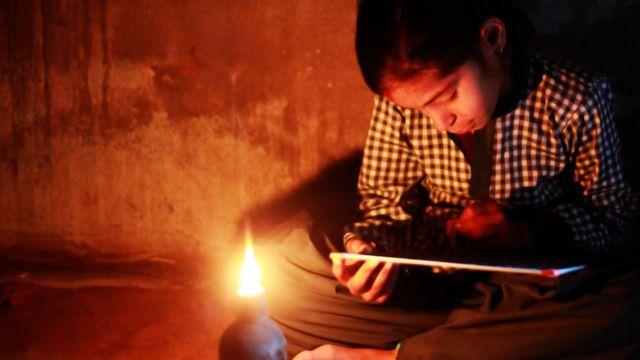 Menina lendo à luz de candeeiro